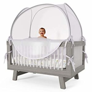 baby standing in crib with crib tent