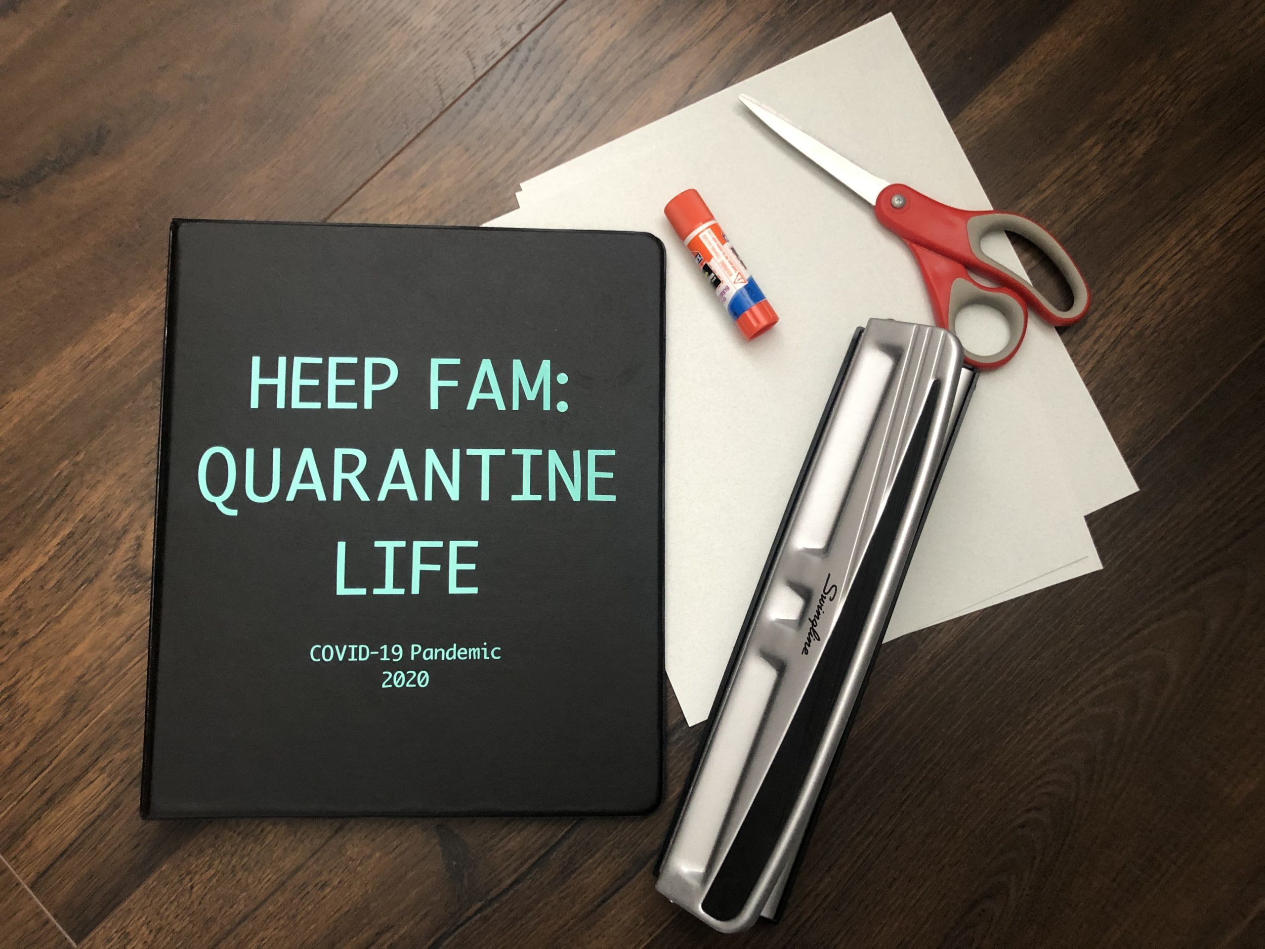 Black quarantine journal with a hole puncher, scissors, and glue stick on a stack of paper on a table