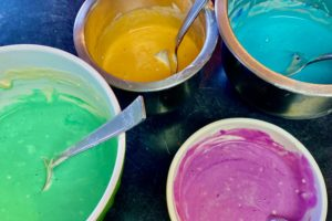 Bowls of pancake batter in four colors: green, orange, blue, and pruple.