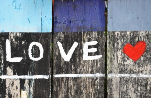 LOVE written in white paint with a red heart on a wooden fence