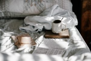 an unmade bed with books and a coffee mug to symbolize the comfort in confinement