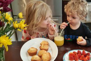 a blonde girl sharing orange juice with two straws with her blonde brother while eating muffins and strawberries