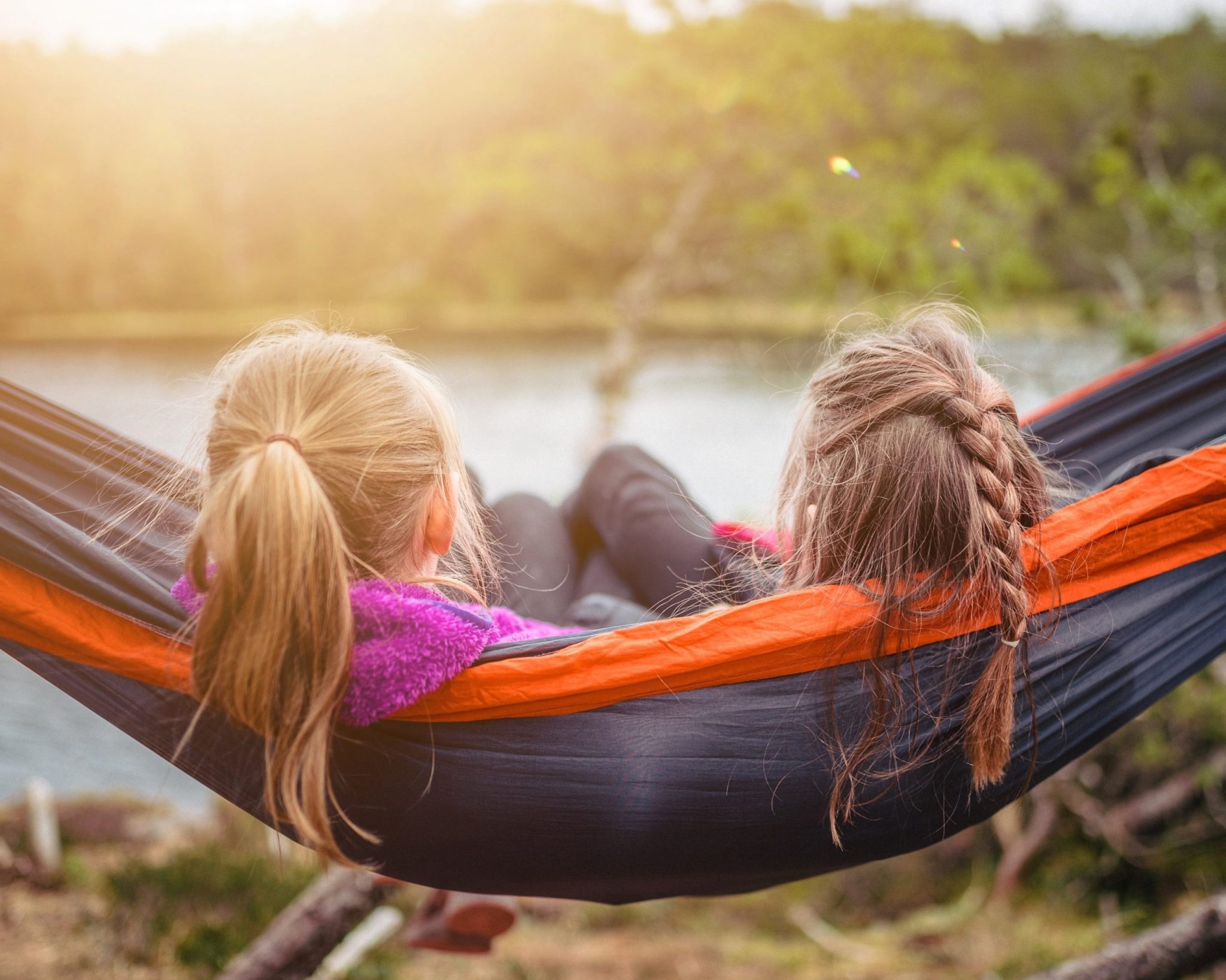 A hammock with two people with long hair sitting together