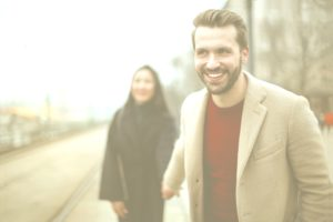 man smiling as he reaches back to hold a woman's hand as they walk down the street