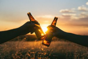 Silhouette of two hands holding glass bottles together in front of a sunset