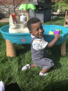 a smiling boy, playing with a water table in the grass