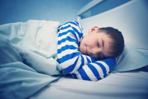 boy in blue and white pajamas asleep in his bed