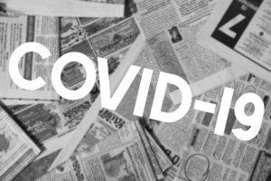 COVID-19 Inscription Across Newspaper Blurred Background. Coronavirus News Concept