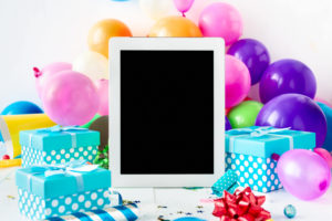 virtual birthday party with a blank tablet screen on a table among balloons and presents