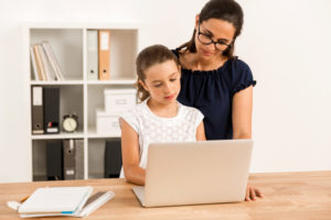 a mom assuming the role of quarantine teacher and helping her child learn