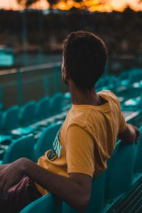 man sitting in empty sports stadium