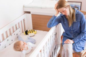 Mom leaning on crib rail as she tries to put baby to sleep.
