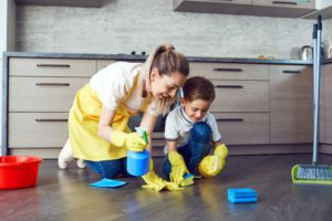 a mother and son using natural cleaning products to clean the floor