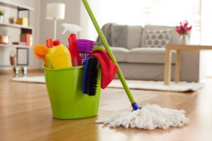 a green plastic bucket full of cleaning supplies with a mop resting against it in a family room setting