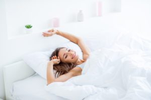 a woman waking up, stretching, under a weighted blanket to improve sleep