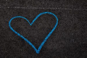 A blue sidewalk chalk heart on asphalt