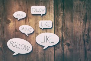 Paper cut speech bubbles with social media concepts on wooden background
