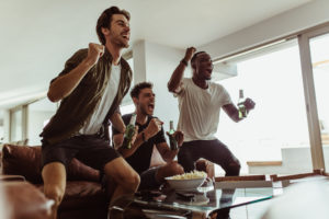 three male friends drinking beer and watching sports on the couch together as they cheer