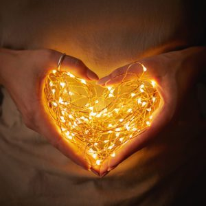 Close-up of lights in the shape of a heart, a woman holding in hands in the dark to symbolize a mother's heart lights the way