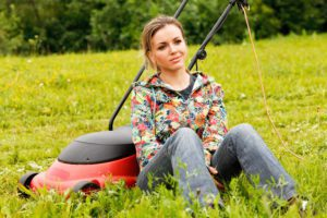 woman smirking as she sits next to a lawn mower