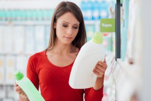 a close up of a woman going green with her cleaning products as she reads the labels on cleaners