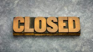 """Gold block letters on a marbled background saying, """"Closed""""."""