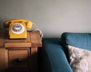 an image of a yellow phone on a wooden side table near a blue couch serving as a reminder to call your mom