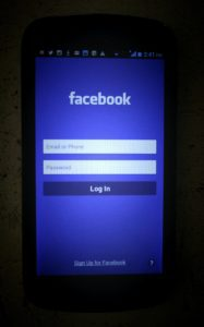 a phone screen lit up by the facebook blue background, on the login page