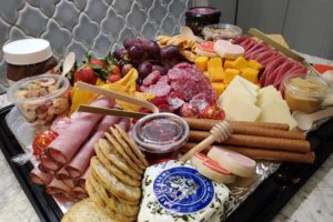 charcuterie board full of meats, cheeses, crackers, and spreads