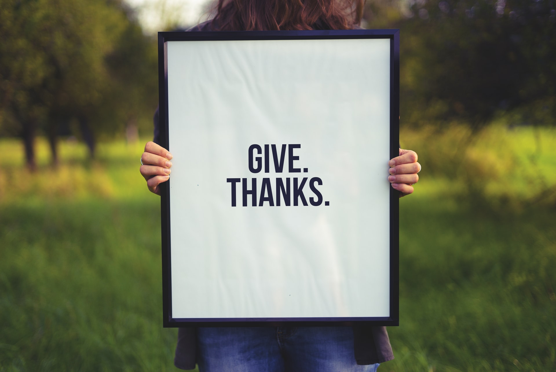 "a person showing gratitude by holding a white sign saying, ""Give Thanks."" in a grassy field."