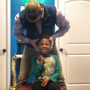 A smiling boy sits in a chair as his neck is adjusted.