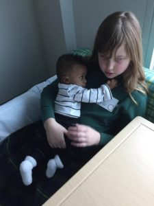 a caucasian girl holding on to her African American baby brother, reminding us that love is color blind
