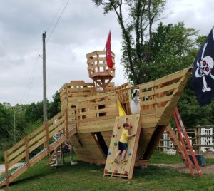 a wooden pirate ship playset complete with a climbing wall, slides, and pirate flags