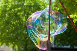 representing summer backyard activities, a close up of a giant bubble maker crafting a huge bubble against the backdrop of green leaves