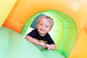 close up of a little boy playing on an inflatable bounce house