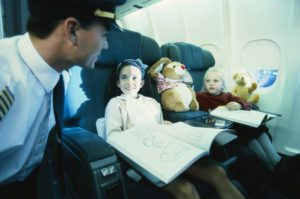 A male flight attendant checking on two girls on the flight as he keeps serving the peanuts