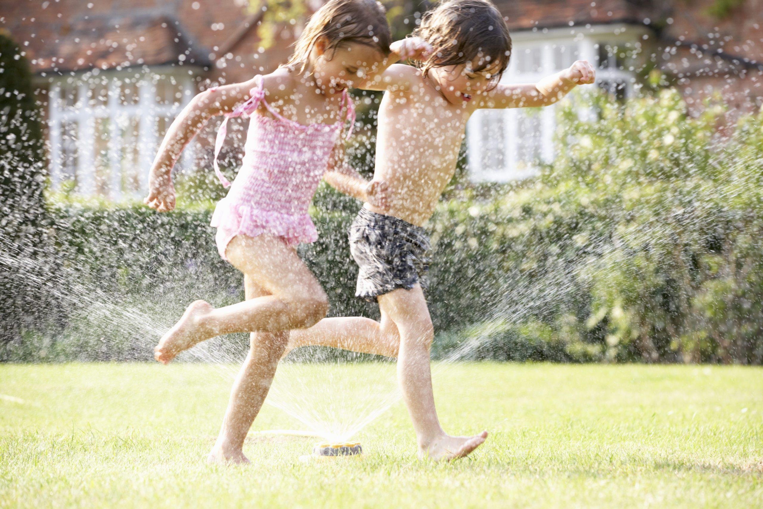 two children running through a garden sprinkler