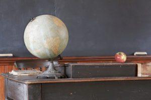 Vintage classroom showing blackboard behind apple and antique globe on teacher's desk