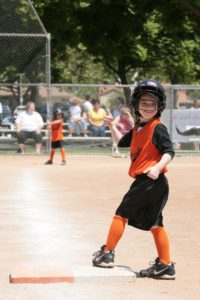 A young girl playing softball, standing on a base as she looks for her mom in the crowds