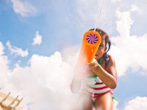 enjoying summer backyard activities, this little girl in a striped swimsuit squirts a water blaster
