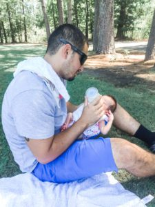 a dad sits on the grass as he bottle-feeds his newborn, symbolic of the support partners give their spouses suffering from postpartum depression
