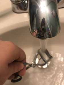 a photo of a woman running hot water on her eyelash curler as it makes it work better per one of the beauty tips she follows