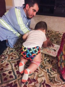 a dad sits sprawls on the floor with his baby as they read a book together