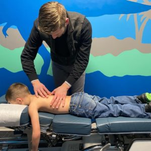 A boy laying on a chiropractor's table having his back adjusted.