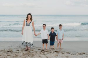 A mom standing on the shore with her three little boys