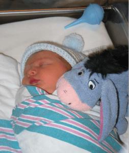 newborn baby boy in a hospital bassinet with a bulb syringe and an Eyesore stuffed animal