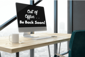 """an office desk by a window with a computer screen that reads, """"Out of Office, Be Back Soon"""" to represent maternity leave"""