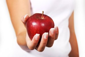 a close up of a woman holding an apple for a snack
