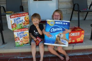 A mom learned pandemic lessons as she shows a photo of her two kids with bulk toilet paper and snacks.