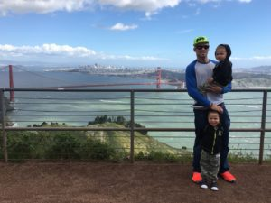 a single dad with his two sons on a hill in front of the Golden Gate Bridge